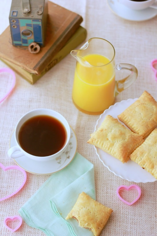 A top view of the pastries on a plate, coffee cup, orange juice and books on a tablecloth