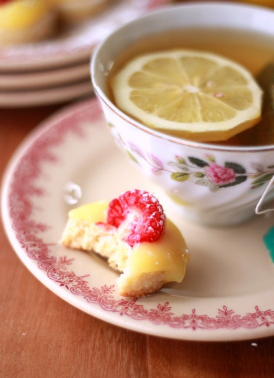 Lemon Curd and Raspberry Tea Cookie on a plate with a bite taken out beside a cup of tea