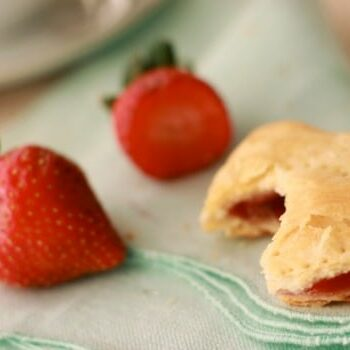 Pastry with a bite taken out and fresh strawberries all on a cloth napkin