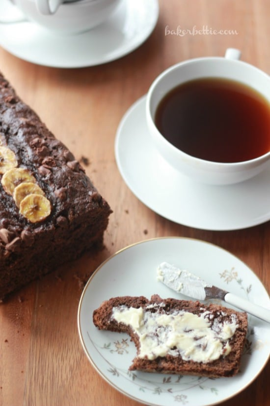 A slice of Dark Chocolate Banana Bread with Cayenne with butter and a cup of coffee
