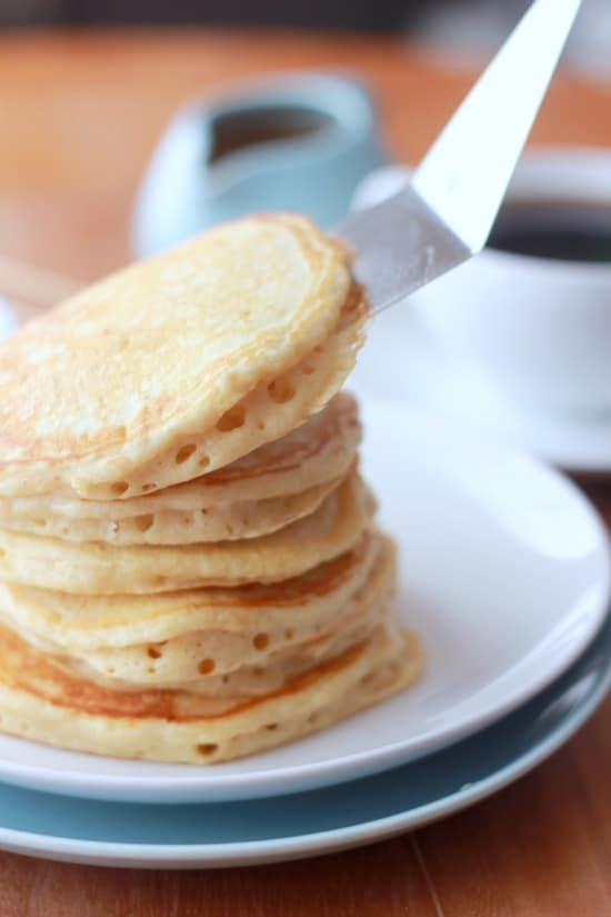 Old Fashioned Sour Milk Griddlecakes being stacked on a plate with a spatula