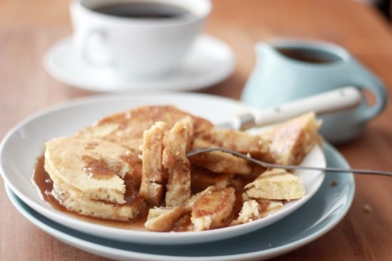 Old Fashioned Sour Milk Griddlecakes with Cinnamon Roll Syrup on a plate being eaten with a fork