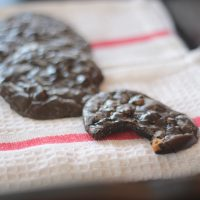 Flourless Dark Chocolate Espresso Cookies with Butterscotch Chips on a tea towel with a bite taken out