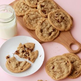 Chocolate chip cookies on wooden platter, one cookie on a plate