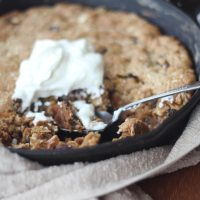 Side angle of Maple Oatmeal Raisin Skillet Cookie with Greek Yogurt dug in with a spoon
