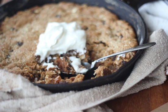 Side view of Maple Oatmeal Raisin Skillet Cookie with Greek Yogurt with a spoon dug in