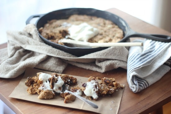 Side angle of Maple Oatmeal Raisin Skillet Cookie with Greek Yogurt on a towel with a portion on a napkin with a spoon