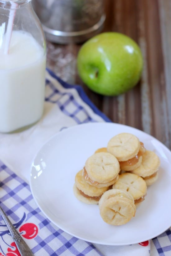 Mini Apple Pie Sandwich Cookies on a plate with a glass of milk