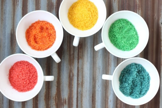 Different colored sugars in individual bowls: red, orange, yellow, green and blue