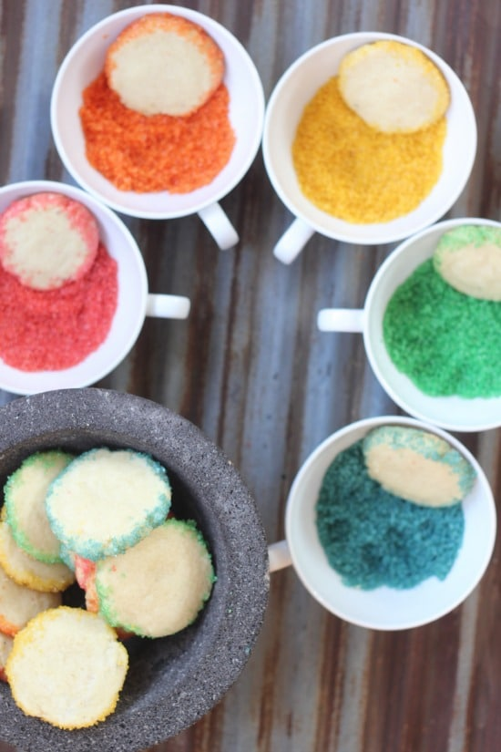 Kaleidoscope Rainbow Cookies placed in a bowl of different colored sugars