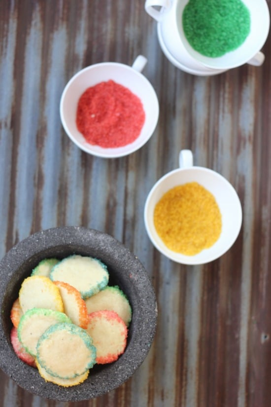 Kaleidoscope Rainbow Cookies in a bowl, different colored sugars in their bowls