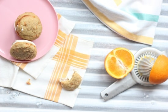 Carrot Cake Whoopie Pies on a plate, juicer with an orange nearby