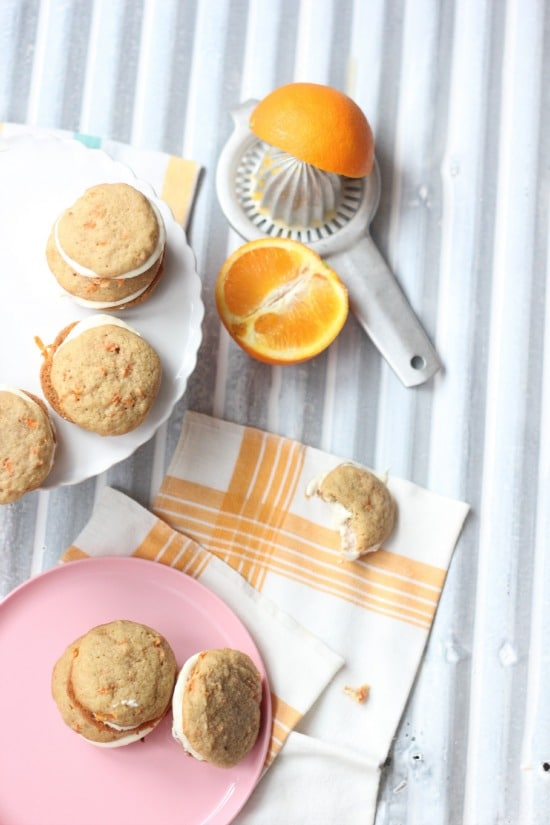 Carrot Cake Whoopie Pies on a plate and cake stand surrounded by tea towels and oranges