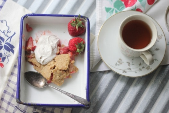 Paleo Strawberry Rhubarb Pie with Coconut Whipped Cream slice on a plate beside a cup of tea