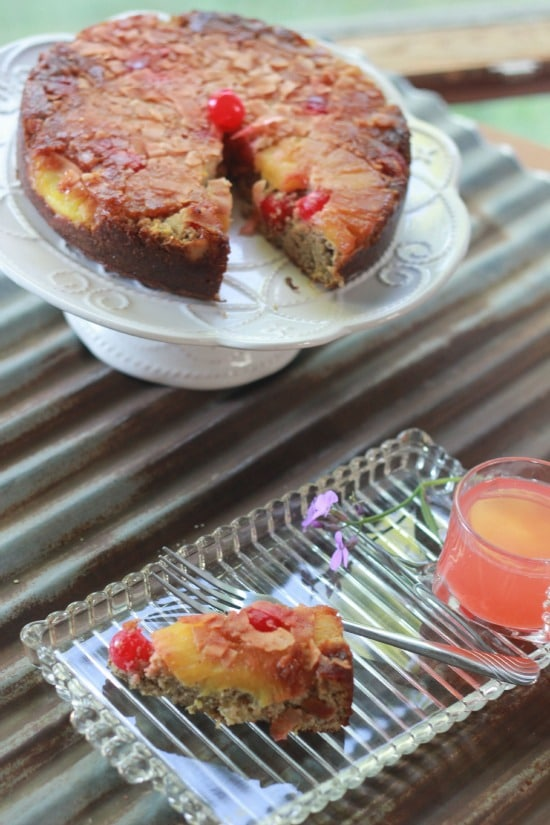 Pineapple upside down cake on a cake plate with a piece taken out