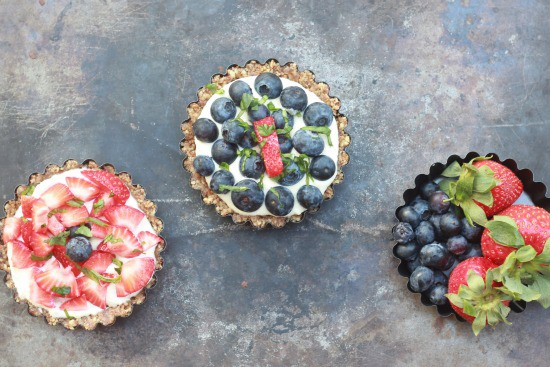 One tart with strawberries on top, one with blueberries and a bowl of blueberries and strawberries