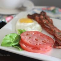 Perfectly Crisp Rosemary Pepper Bacon on a plate with a fried egg and tomato slices