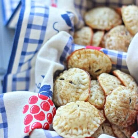 Mini Chocolate Hand Pies in a basket with a floral cloth