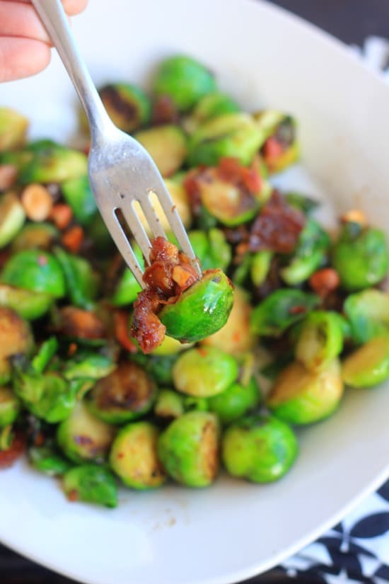 Roasted Brussel Sprouts with Dates and Almonds being eaten with a fork