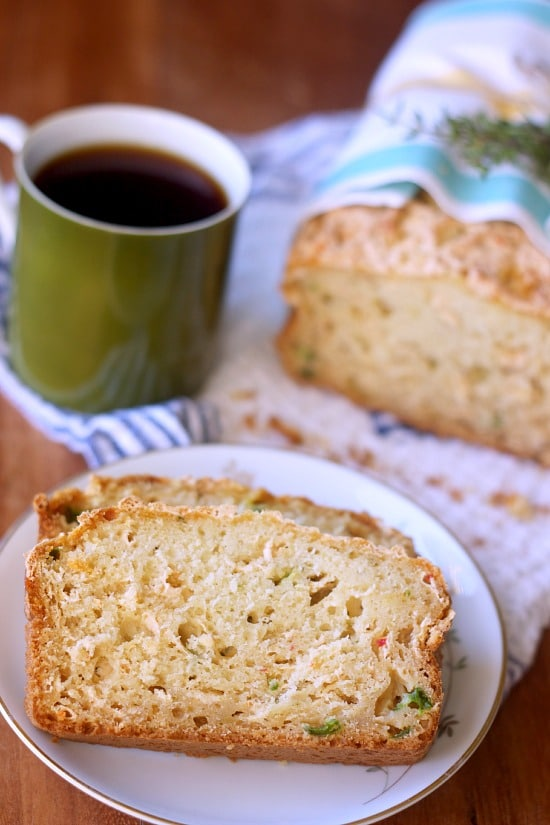 Sliced Cheddar Jalapeno Thyme Quick Bread on a plate with a cup of coffee