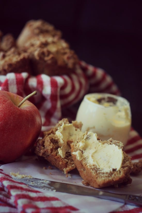 Apple Streusel Muffin cut in half with a slab of butter