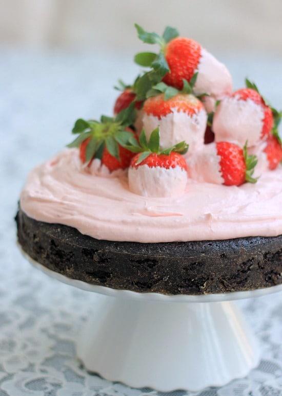 White Chocolate Covered Strawberry and Dark Chocolate Fudge Cake on a cake stand