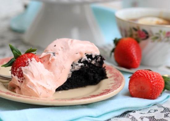 A slice of White Chocolate Covered Strawberry and Dark Chocolate Fudge Cake