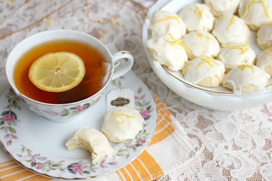 Lemon Goat Cheese Cookies with a bite taken out and a cup of tea