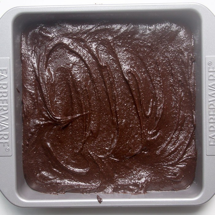 Raw brownie batter in square pan