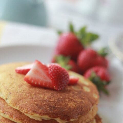 Stack of pancakes on a plate with strawberries on top