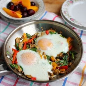 Roasted veggies in a skillet topped with over-easy eggs
