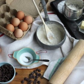 Various raw ingredients setup nicely on a table cloth: eggs, chocolate chips, sugar, etc