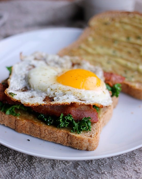 Kale, bacon and an over-easy egg on sliced bread