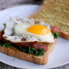 Kale, bacon and an over-easy egg with aioli on sliced bread