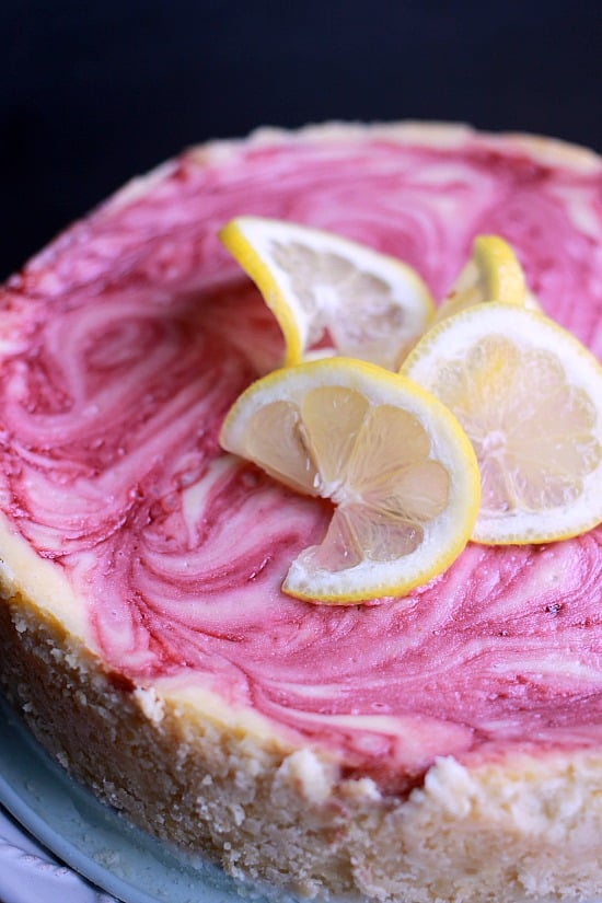 Raspberry Swirled Lemon Cheesecake with lemon slices as decoration on top