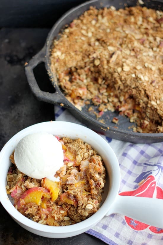 A serving of Peach Rhubarb Skillet Crisp in a bowl with ice cream
