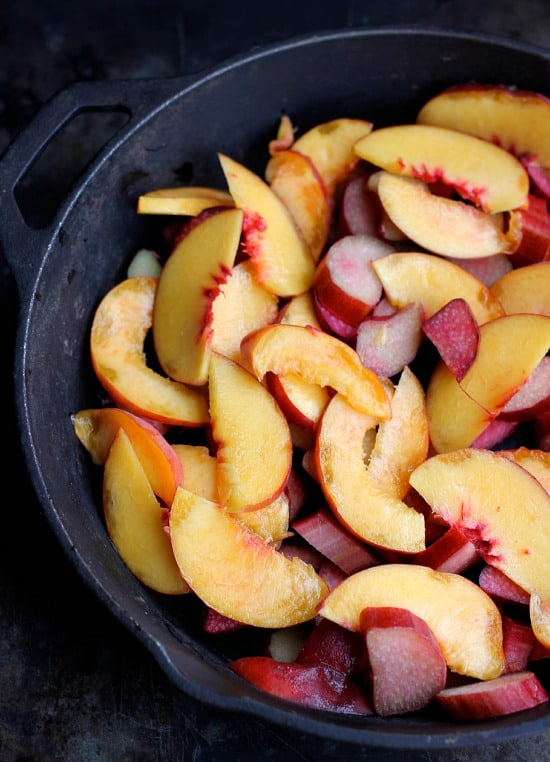 Raw slices on rhubarb and peaches in a skillet