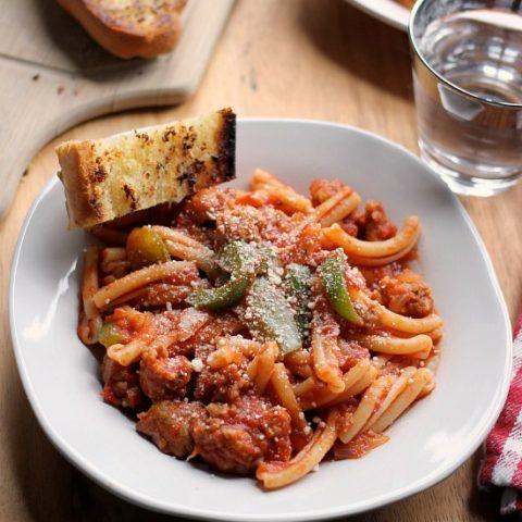Spicy Sausage Pasta Marinara in a bowl with a slice of garlic bread