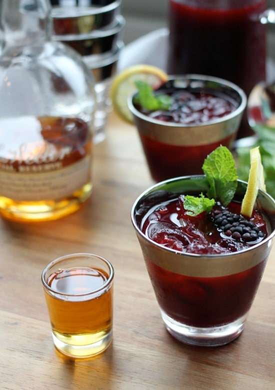 Bourbon Blackberry Mint Lemonade in a glass beside a shot glass of bourbon