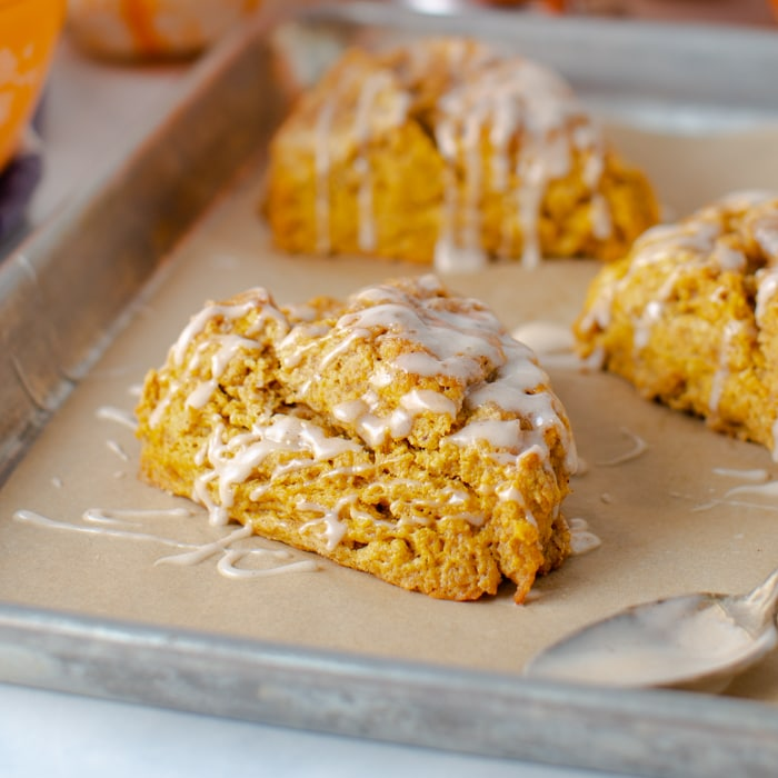 sheet pan with pumpkin scones with cinnamon glaze drizzled on top