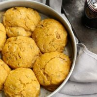 Pumpkin Scones with Sage in a baking pan beside a jar of Spicy Cherry Jam