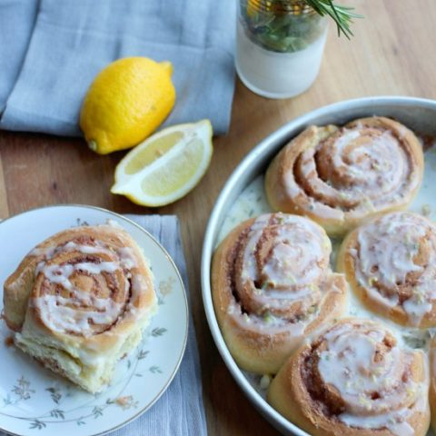 A Rosemary Lemon Cinnamon Rolls on a plate drizzled with glaze