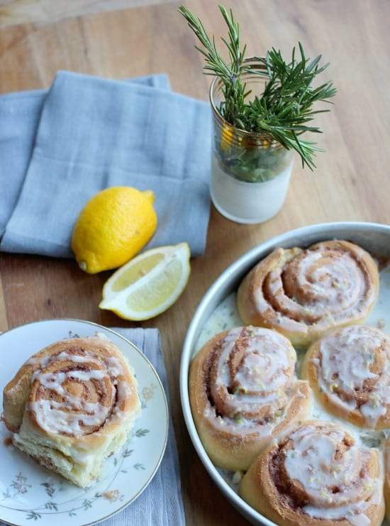 Rosemary Lemon Cinnamon Rolls in a pan drizzled with glaze