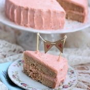 A slice of Strawberry birthday cake with strawberry vanilla bean icing