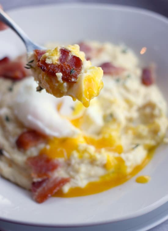 A spoonful of Creamy Breakfast Polenta in a bowl with bacon and a poached egg on top