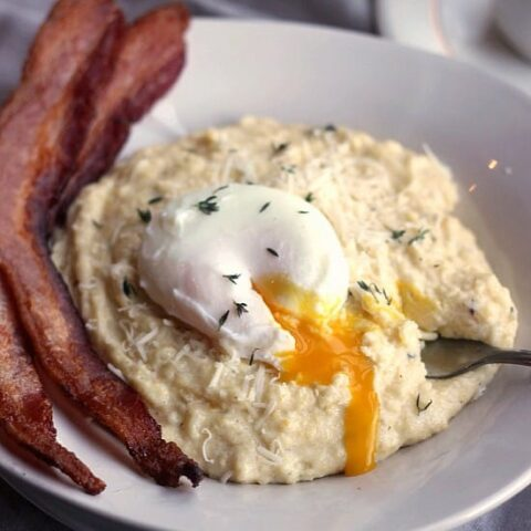 Creamy Breakfast Polenta with Asiago, Thyme, Bacon, and Poached Eggs