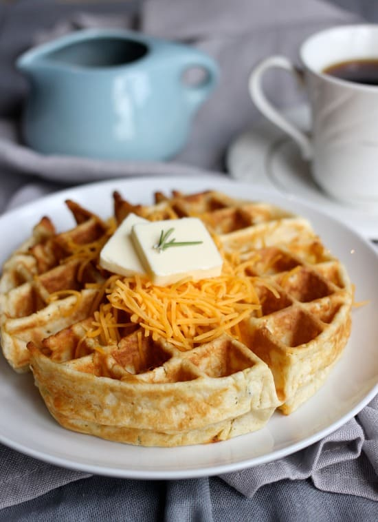 Cheddar and Rosemary waffle with shredded cheddar and pad of butter on top