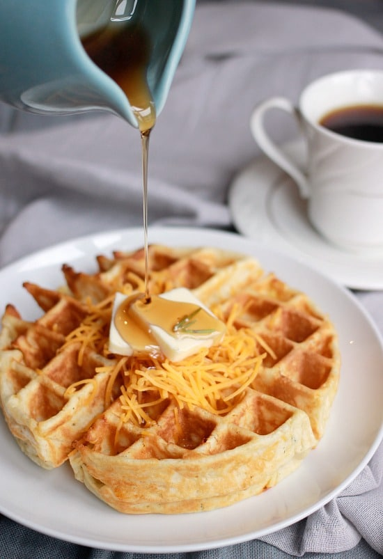 Cheddar and Rosemary waffle with shredded cheddar, pad of butter and syrup on top