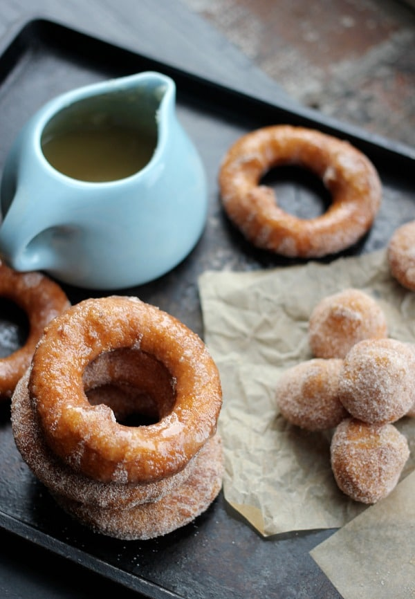 Puff Pastry Donuts rings stacked up with donut holes dipped in cinnamon sugar beside a cup of Bourbon Glaze