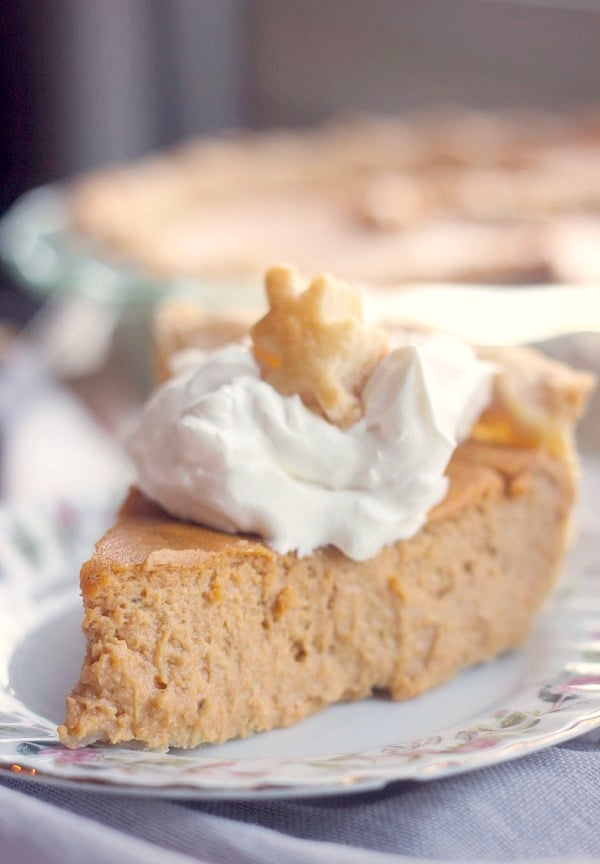 A slice of pumpkin pie with whipped cream on top